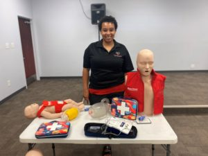 Ludie Jones, a short haired black woman pictured with her CPR and first aid training equipment